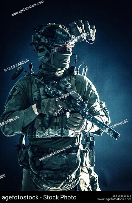 Anti-terrorist squad fighter, army elite forces soldier in combat uniform and tactical ammunition, armed mini submachine gun, wearing night-vision device