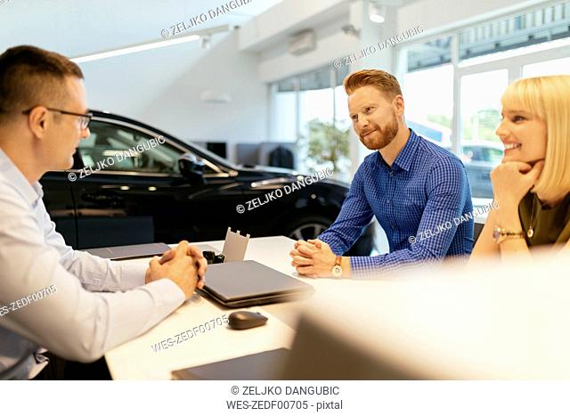 Salesperson advising couple in car dealership