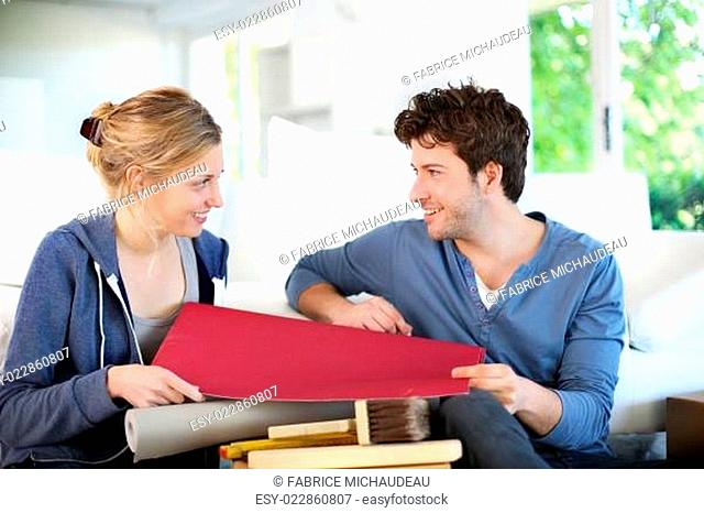 Young couple choosing wallpaper color for new apartment