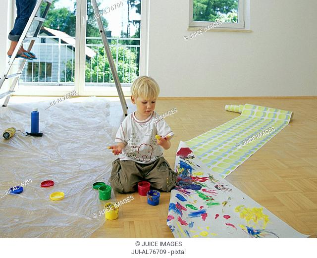 View of a young boy fingerpainting on a roll of wallpaper