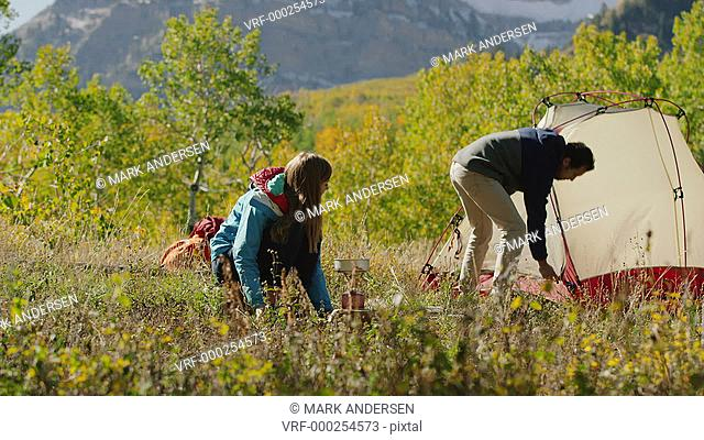 Wide panning shot of couple kissing with food cooked on camping stove / American Fork Canyon, Utah, United States