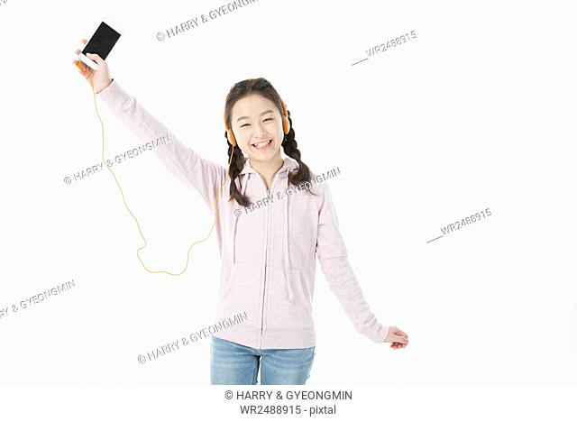 Smiling school girl in casual clothes listening to music on MP3 player