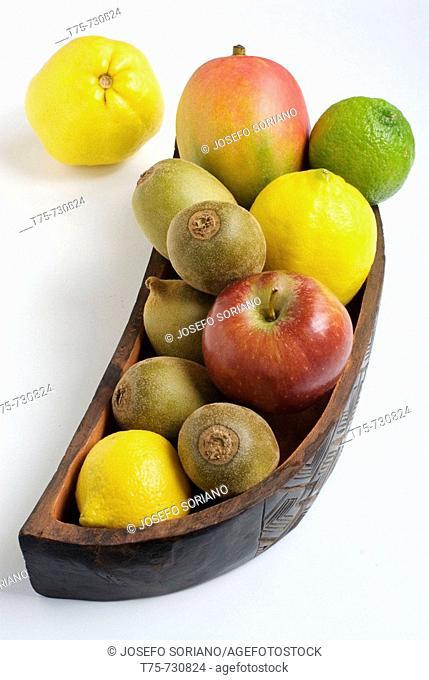 Fruit bowl with a lime, lemons, a mango, an apple and kiwis