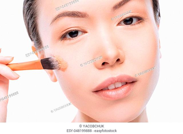 Applying make up. Pretty good looking young woman using cosmetic brush and making the skin tone perfect while applying make up