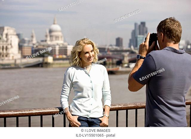 A middle-aged man taking a photograph of his partner next to the river Thames