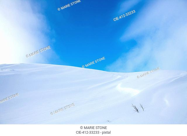Snow-covered hill under blue sky