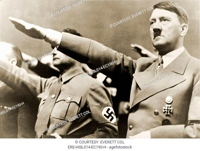 Adolf Hitler, giving Nazi salute. To Hitler's right is Rudolph Hesse. 1939