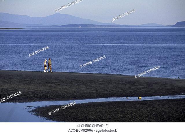 Qualicum Beach Couple walks along beach in morning, Vancouver Island, British Columbia, Canada