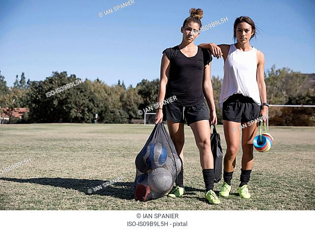 Women on football pitch carrying footballs in net sack