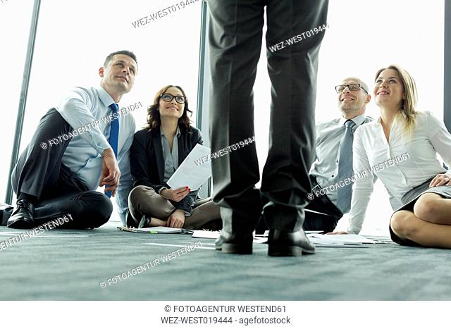 Businesspeople sitting on floor looking up at colleague