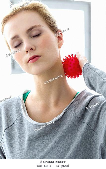 Young woman using massage ball on neck