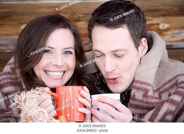 Couple wrapped in blanket drinking tea