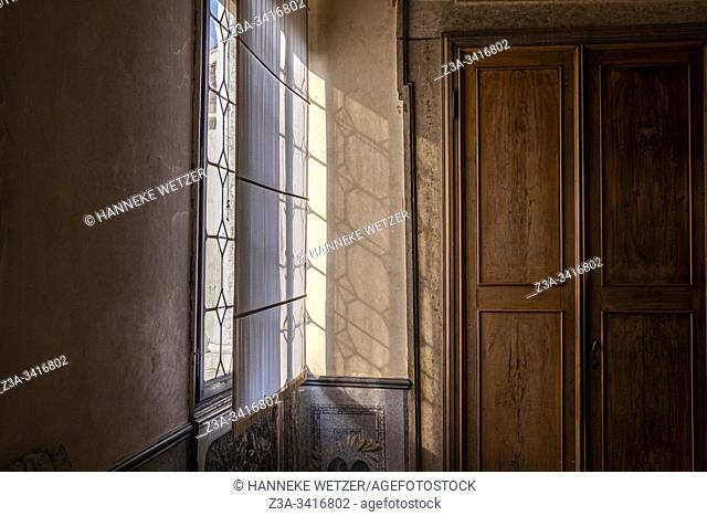 Old interior with wooden door and sunlight through a window in Venice, Italy