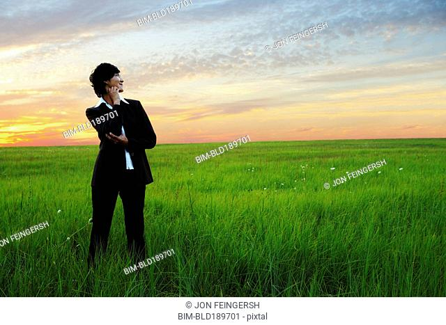 Asian businesswoman standing in field