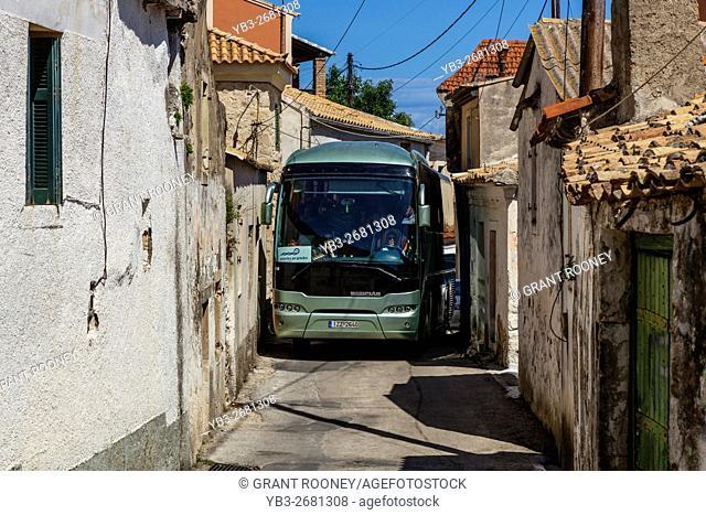 A Coach Drives Through The Narrow Streets Of Lakones High Above The Seaside Village Of Paleokastritsa, Corfu Island, Greece