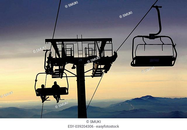 Ski-lift transports skiers to the top of the mountain and the sun goes down