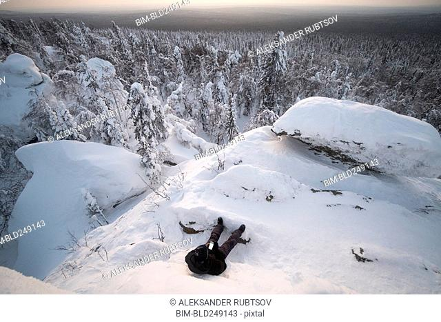 Caucasian man laying in snow texting on cell phone