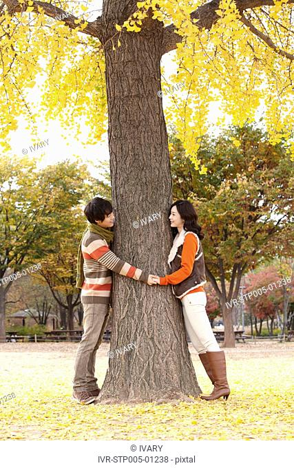 Young Couple Standing Around Tree Holding Hand
