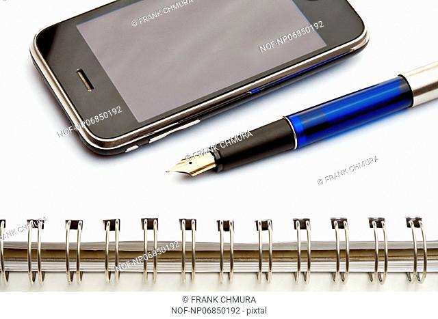 extreme close up of a fountain pen, spiral notebook and cell phone