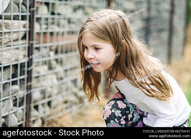 Young girl crouching down and looking for bugs in a rock wall