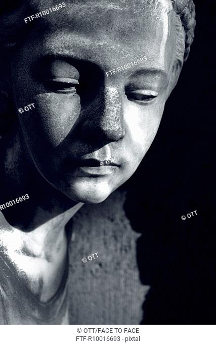 A grayscale image of statue of a boy