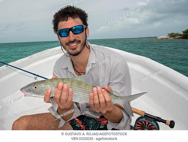 A fly fisherman Man holding Bonefish . los roques Venezuela