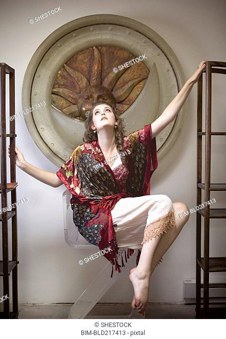 Woman floating between empty bookshelves in ornate room