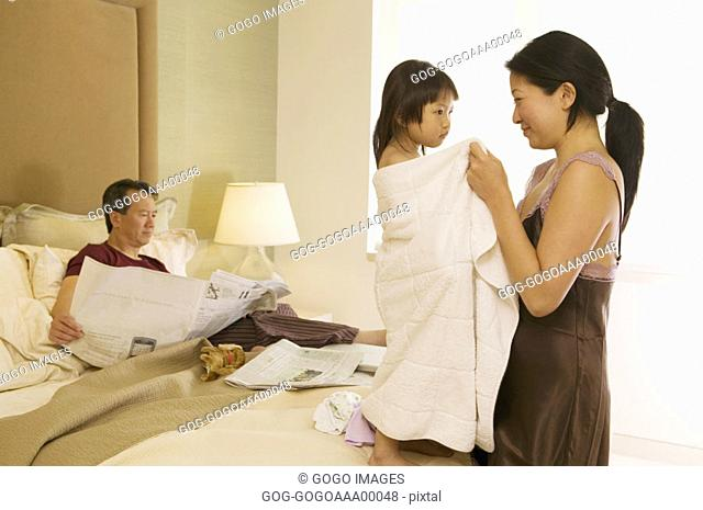Mother smiling at daughter 4-5, father reading newspaper in background