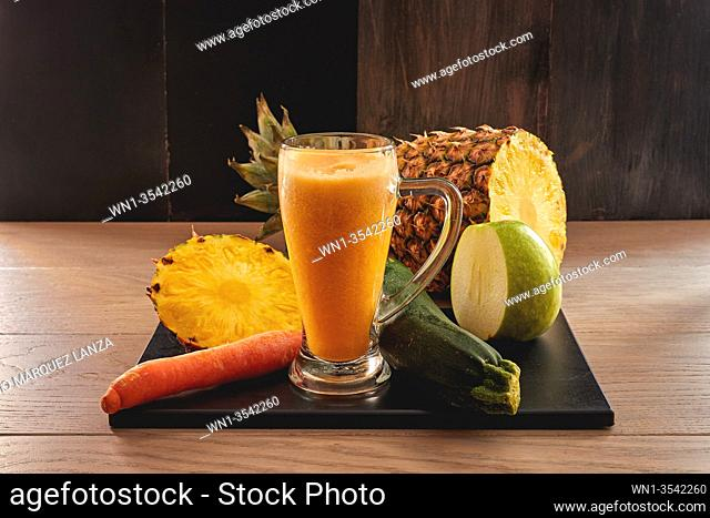 veggie juicy of pineapple, apple, cucumber and carrot in a dark background
