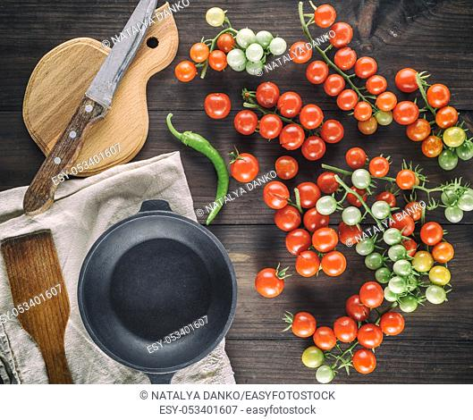 cast iron round frying pan and ripe red cherry tomatoes on a brown wooden table, top view