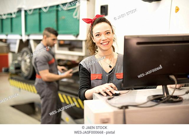 Mechanics working in calibrate the wheels with computer, smiling woman
