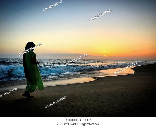 A woman walks at sunset in the Pacific Ocean coast in the beach in Todos Santos, Baja California Sur, Mexico