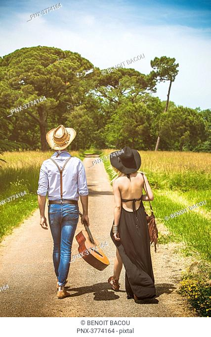 Young couple Hipster ride in the countryside, a guitar in hand