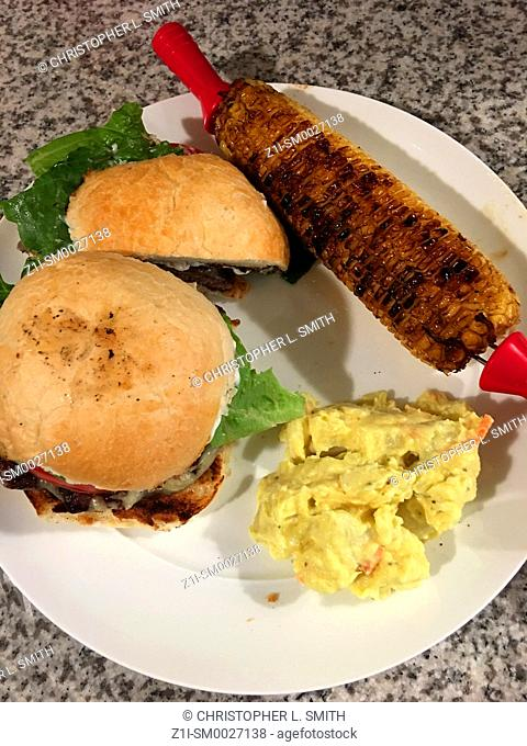 July 4th American meal - Burger on a toasted bun with potato salad and corn