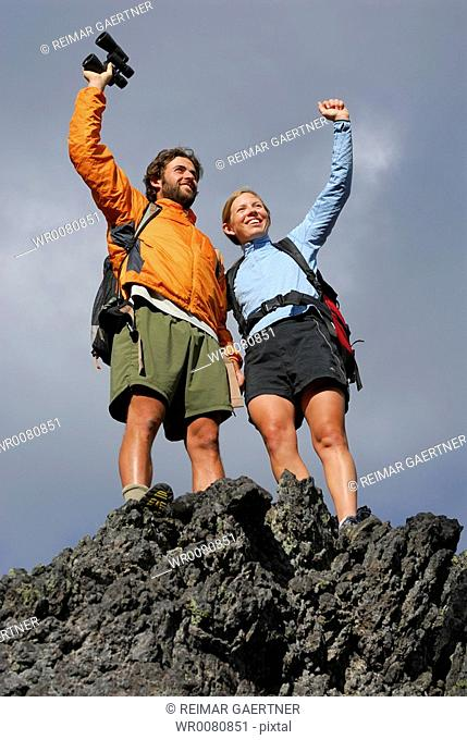 Male and female hikers cheering and waving at the summit