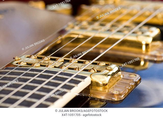The strings and pickups of a Gretsch guitar, detail with limited depth of focus