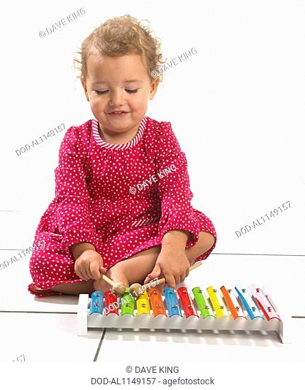 Young girl (2 years) playing with colourful toy xylophone