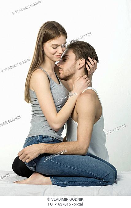 Romantic couple embracing while sitting on bed against white background
