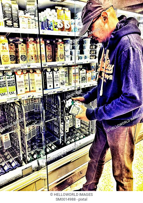 Middle aged man buying milk in Swedish supermarket