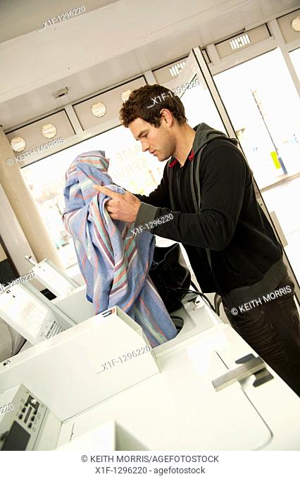 white caucasian male man washing bhis clothes in a Launderette, UK
