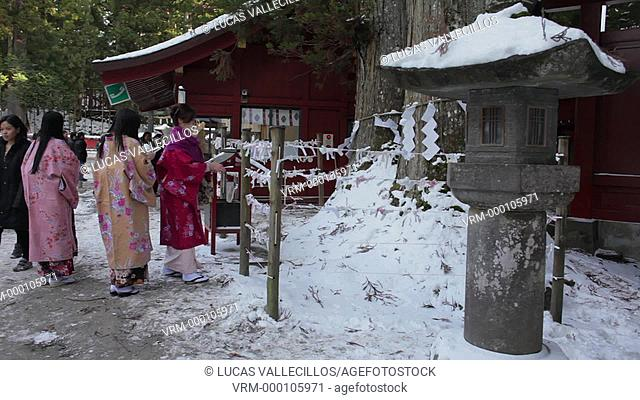 Friends in traditional dress hanging invocations to the fortune,Futarasan Shrine, Nikko,Japan