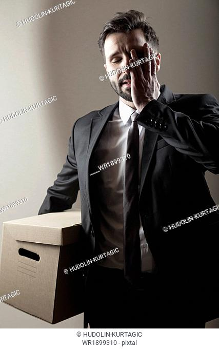 Businessman carrying cardboard box