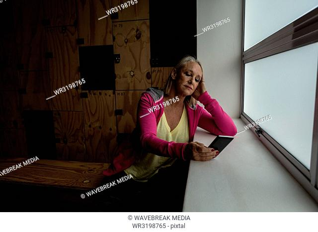 Mature woman using mobile phone in the gym