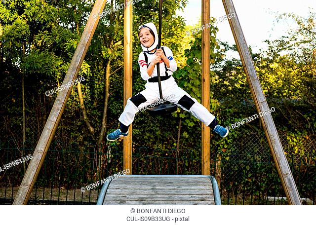 Portrait of boy in astronaut costume riding on playground zip wire