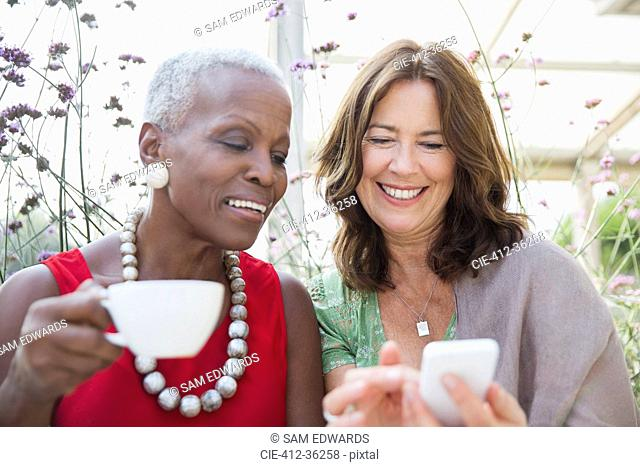 Smiling mature women friends drinking coffee and using cell phone