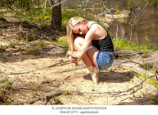15 year old blond girl in casual clothing balancing on toe shoes, in a crouch position