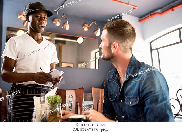 Waiter in restaurant taking customers order