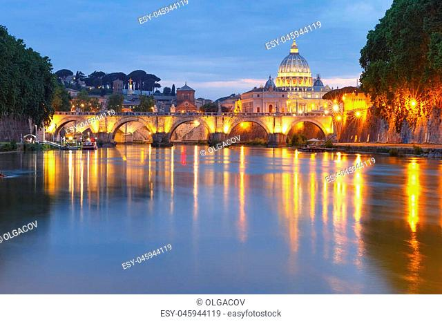 Saint Angel bridge and Saint Peter Cathedral with a mirror reflection in the Tiber River during evening blue hour in Rome, Italy