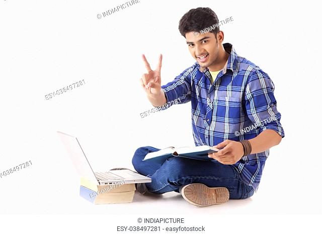 Young Man Shows Victory front of a Laptop