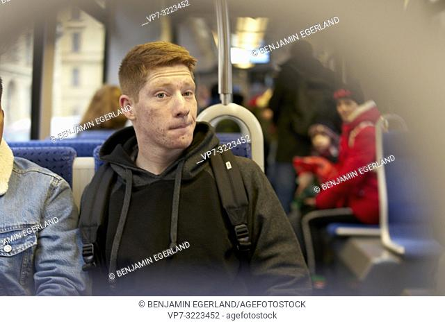 man sitting in public transport, streetcar, tram, in Munich, Germany